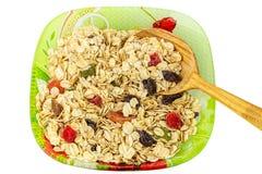 Hafer blättert mit Trockenfrüchten auf Platte mit dem hölzernen Löffel ab, lokalisiert auf weißem Hintergrund, Draufsicht Stockfotos