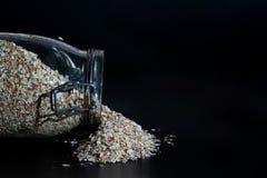 Hafer, die heraus von einem Glas verschüttet werden lizenzfreie stockbilder