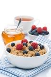 Haferbrei mit frischen Beeren und Honig, eine Schale schwarzer Tee Stockbild