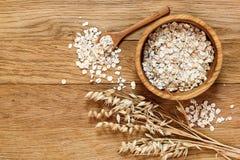 Haferflocken und Haferohren des Kornes auf einem Holztisch stockbilder