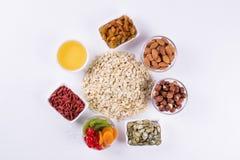 Haferflocken und verschiedene köstliche Bestandteile zum gesundes Frühstück, Lizenzfreies Stockfoto