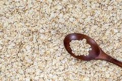 Hafermehl auf hölzernem Löffel auf einem Hafermehl-Hintergrund lizenzfreies stockfoto