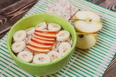 Hafermehl-Brei mit Apple und Bananen-Scheiben in der grünen Schüssel Stockfotografie