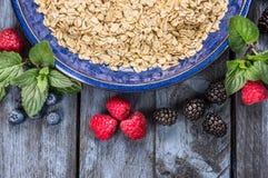 Hafermehl in der blauen Schüssel mit Beeren auf rustikalem hölzernem Hintergrund, Draufsicht, gesundes Lebensmittel Stockbild