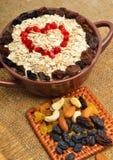 Hafermehl in der keramischen Platte, im Löffel, in den Rosinen, in den Acajoubäumen und in den Mandeln Lizenzfreies Stockfoto