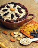 Hafermehl in der keramischen Platte, im Löffel, in den Rosinen, in den Acajoubäumen und in den Mandeln an Lizenzfreie Stockbilder