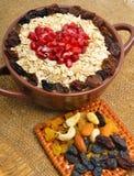 Hafermehl in der keramischen Platte, im Löffel, in den Rosinen, in den Acajoubäumen und in den Mandeln Stockfoto
