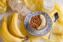 Hafermehl mit Banane, Rosinen, Mandeln und Milch Lizenzfreie Stockbilder