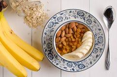 Hafermehl mit Banane, Rosinen, Mandeln und Milch Lizenzfreies Stockbild
