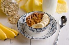 Hafermehl mit Banane, Rosinen, Mandeln und Milch Stockfotos