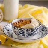 Hafermehl mit Banane, Rosinen, Mandeln und Milch Stockfotografie
