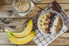 Hafermehl mit Bananen, Moosbeere, chia Samen, Kokosnussfetzen, alm stockfotografie