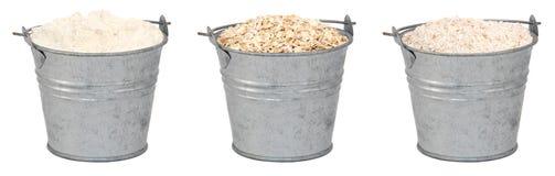 Hafermehl und Mehl in den Miniaturblecheimern Lizenzfreie Stockfotos
