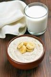 Hafermehlbrei mit Bananenscheiben und Glas Milch Stockbild