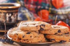 Hafermehlplätzchen auf einem hölzernen Hintergrund mit einem Tasse Kaffee und Waldbeeren auf dem Hintergrund eines warmen Schals Lizenzfreie Stockfotos