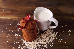Hafermehlplätzchen auf einem Hintergrund von Hafern, nahe bei einem Glas Milch, auf Weinlesebrett Stockbilder