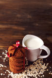 Hafermehlplätzchen auf einem Hintergrund von Hafern, nahe bei einem Glas Milch, auf Weinlesebrett Stockbild