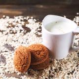 Hafermehlplätzchen auf einem Hintergrund von Hafern, nahe bei einem Glas Milch, auf Weinlesebrett Lizenzfreie Stockfotos