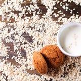 Hafermehlplätzchen auf einem Hintergrund von Hafern, nahe bei einem Glas Milch, auf Weinlesebrett Lizenzfreies Stockbild