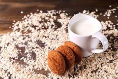 Hafermehlplätzchen auf einem Hintergrund von Hafern, nahe bei einem Glas Milch, auf Weinlesebrett Lizenzfreies Stockfoto