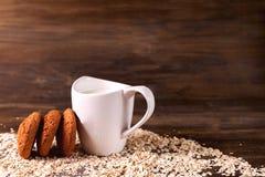 Hafermehlplätzchen auf einem Hintergrund von Hafern, nahe bei einem Glas Milch, auf Weinlesebrett Stockfoto