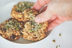 Hafermehlplätzchen des strengen Vegetariers mit Daten und Kürbiskernen in der Hand heal stockfoto