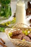 Hafermehlplätzchen in einem Korb mit einer Flasche Milch und wilden Blumen Stockbild