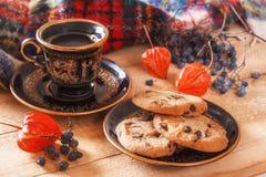 Hafermehlplätzchen und -kaffee auf einem Holztisch mit Physalis- und Waldbeeren auf dem Hintergrund eines warmen Schals Lizenzfreie Stockbilder