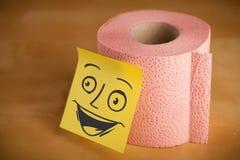 Haftnotiz mit smileygesicht sticked auf einem Toilettenpapier Lizenzfreies Stockfoto