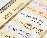 Haga calendarios la página con una mano roja del lápiz que escribe el 14 de febrero de 2013 Imágenes de archivo libres de regalías