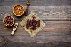 Haga el chocolate El polvo de cacao en cuenco cerca de granos de cacao y los pedazos de chocolate en la opinión superior del fond imagenes de archivo