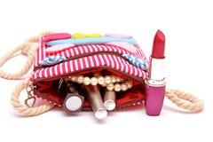 Haga el esmalte de uñas del lápiz labial del equipo que sale de la muchacha bolso práctico Foto de archivo