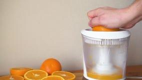 Haga el zumo de naranja fresco con el juicer eléctrico almacen de metraje de vídeo