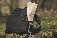 Haga excursionismo con el teléfono y trace en el bolsillo en el tocón imagen de archivo libre de regalías