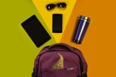 Haga excursionismo con los accesorios, la tableta, el teléfono, vidrios y una taza terma en un fondo brillante Equipo del estudia Imagen de archivo libre de regalías