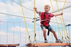 Haga frente a al niño del pelo rubio que juega el curso de la cuerda al aire libre
