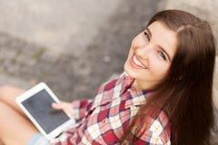 Haga frente al retrato de la mujer joven que usa una PC de la tableta Imagen de archivo libre de regalías