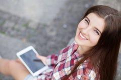 Haga frente al retrato de la mujer joven que usa una PC de la tableta Foto de archivo libre de regalías