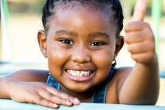 Haga frente al tiro de la muchacha africana que hace los pulgares para arriba al aire libre Imagenes de archivo