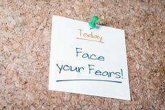 Haga frente a su recordatorio de los miedos para el hoy en el papel fijado en Cork Board fotografía de archivo
