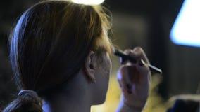 Haga frente a Visagiste modelo con una cara grande del polvo del cepillo en el crepúsculo metrajes