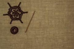 Haga a ganchillo el cordón del tapetito con el gancho de ganchillo y el hilo de algodón en el fondo de lino Foto de archivo libre de regalías