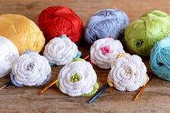 Haga a ganchillo el equipo de las flores, madejas del hilo de algodón, ganchos de diverso tamaño en viejo fondo de madera Rosas h Foto de archivo libre de regalías