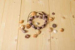 Haga a ganchillo las gotas, las piedras del mar y las conchas marinas hechas a mano en una etiqueta de madera Foto de archivo