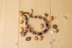Haga a ganchillo las gotas, las piedras y las cáscaras hechas a mano del mar en una luz de madera Fotografía de archivo