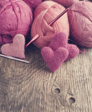 Haga a ganchillo los corazones y el hilado rosados en fondo de madera. Fotos de archivo libres de regalías