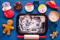 Haga la galleta del pan de jengibre por el Año Nuevo 2018 Hombre de pan de jengibre, rodillo, harina en maqueta de madera azul de Imagenes de archivo
