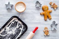 Haga la galleta del pan de jengibre por el Año Nuevo 2018 Hombre de pan de jengibre, rodillo, harina en maqueta de madera gris de Imagenes de archivo