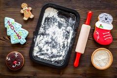 Haga la galleta del pan de jengibre por el Año Nuevo 2018 Hombre de pan de jengibre, rodillo, harina en maqueta de madera oscura  Imágenes de archivo libres de regalías
