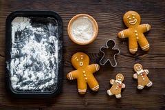 Haga la galleta del pan de jengibre por el Año Nuevo 2018 Hombre de pan de jengibre, rodillo, harina en maqueta de madera oscura  Fotografía de archivo